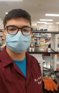 John Asmus working in the biology lab, in a mask