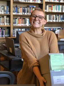 History major carrying archive boxes on UMW trip to National Archives